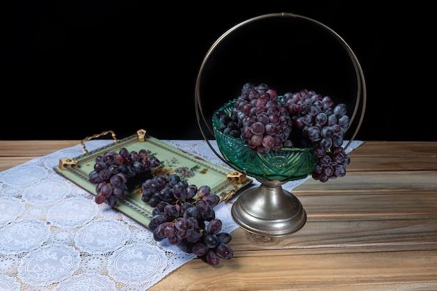 Winogrona na stole ze starą miską owoców