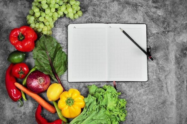 Winogrona, papryka, zielenie, cytryna, pomidor i pusty notatnik na marmurowym tle.