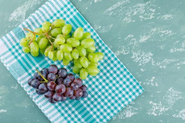 Winogrona płasko leżały na tle tkaniny piknikowej i tynku