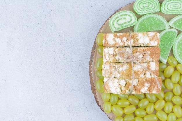 Winogrona, plastry ciasta i marmolady na desce.