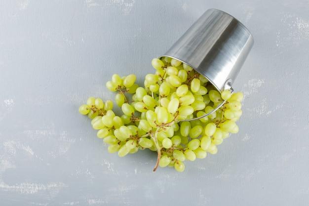 Winogrona rozsypane z małego płaskiego wiaderka leżały na tynku