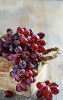 Winogrona w drewnianym pudełku na starym drewnianym stole