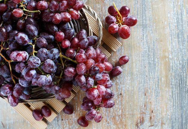 Winogrona w drewnianym pudełku na widok z góry na stary drewniany stół