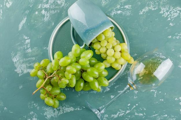 Winogrona w filiżance z napojem płasko leżały na tle tynku i tacy