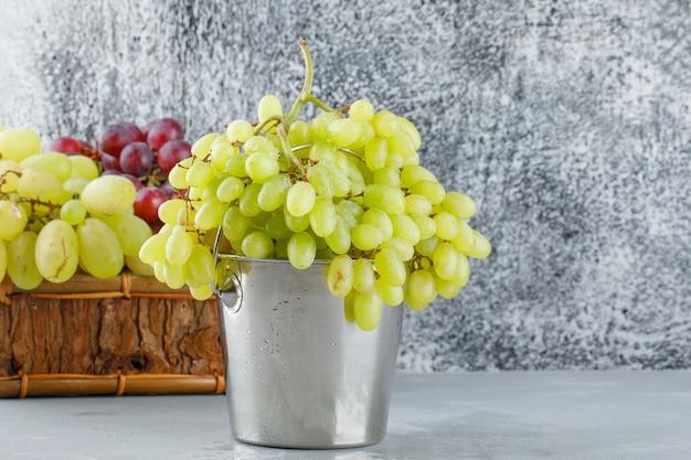 Winogrona w mini wiaderku i koszu na tynku i nieczysty szary.