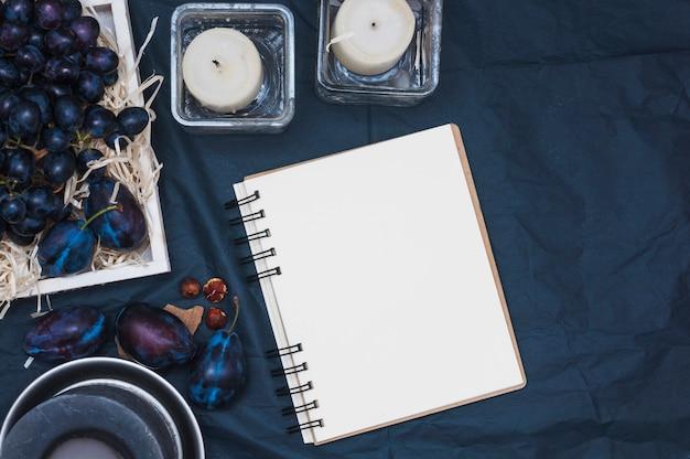 Winogrona w skrzyni ze śliwkami; świece i puste spirala notatnik na obrus