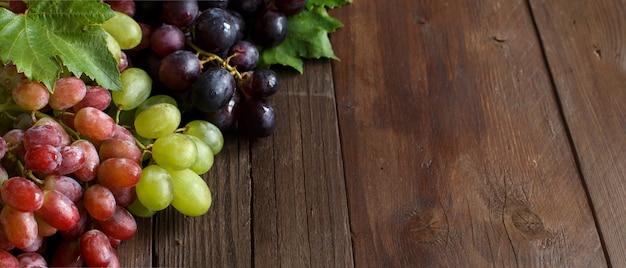 Winogrona z liśćmi na ciemnym drewnianym stole