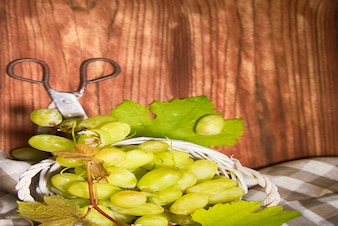 Winogrona z liśćmi na drewnianym tle