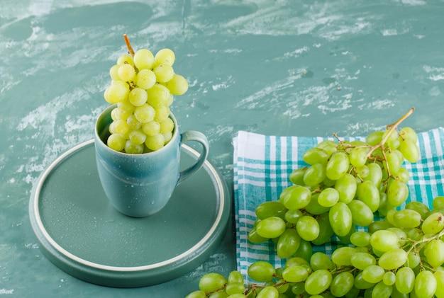 Winogrona z tacą w filiżance na tle tkaniny piknikowej i tynku, wysoki kąt widzenia.