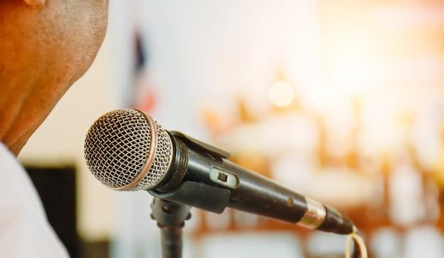 Wiodący człowiek otwiera mowę mikrofonem.