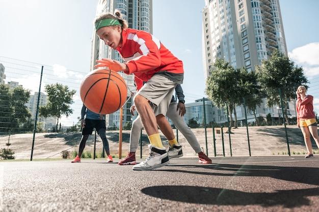 Wiodący gracz. przyjemny młody człowiek bawiący się piłką podczas gry z przyjaciółmi