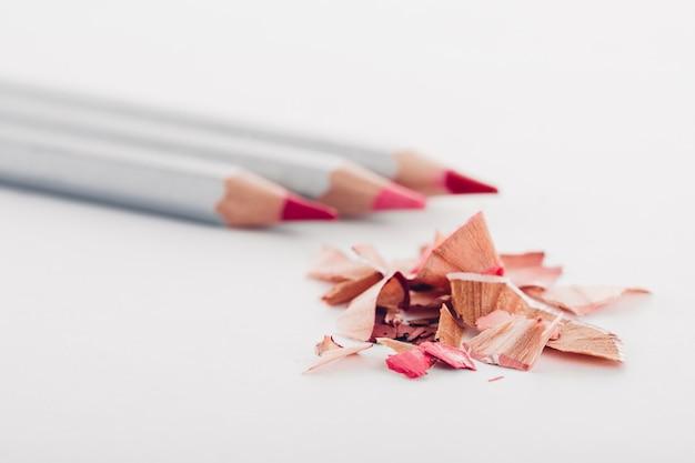 Wióry kosmetyczne różowy ołówek i kolorowe kredki na białym tle