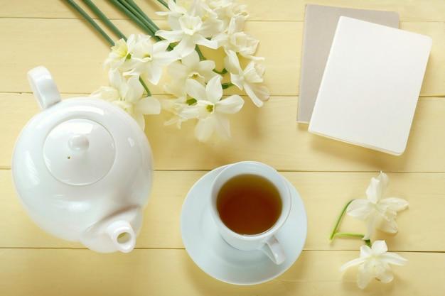 Wiosenna herbata. płaski leżał. notatnik, biały czajniczek, filiżanka herbaty, bukiet białych żonkili na żółtym tle