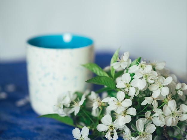 Wiosenna herbata z płatkami kwiatów wiśni na niebieskim tle