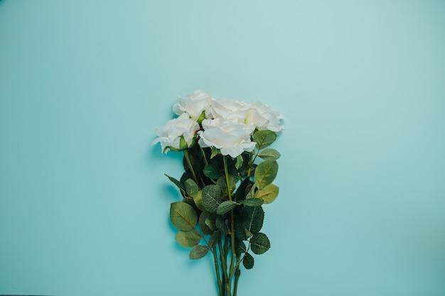 Wiosenna karta świeżości z miejsca kopiowania. białe róże z zielonymi liśćmi. bukiet pięknych białych róż z długą łodygą.