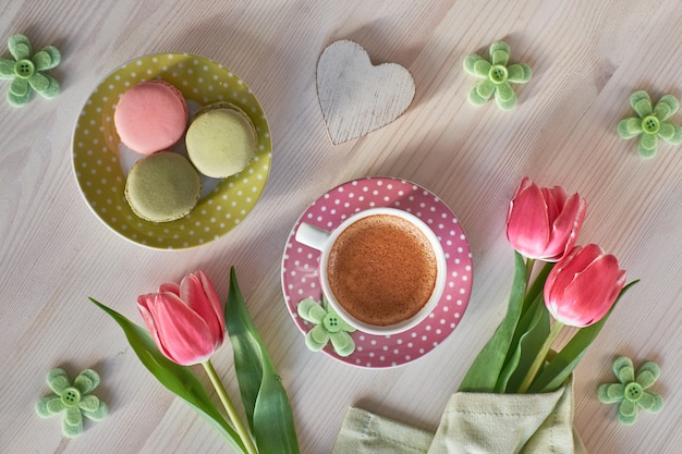 Wiosenna kawa tło. makaroniki, espresso w różowej filiżance, frezje i różowe tulipany