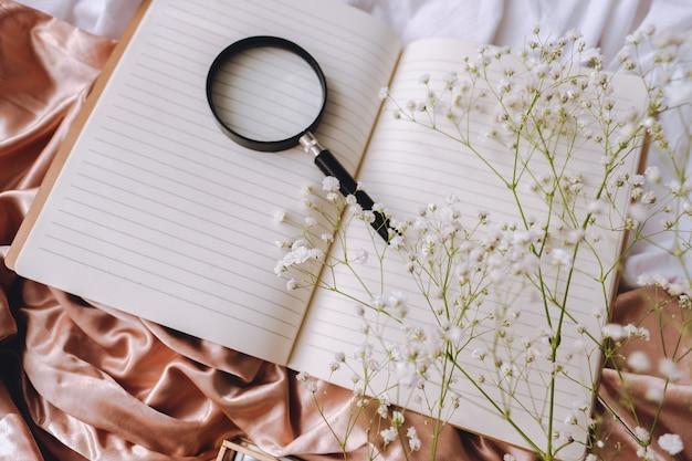 Wiosenna kompozycja, białe kwiaty łyszczec z notatnikiem i lupą na złotej satynowej tkaninie