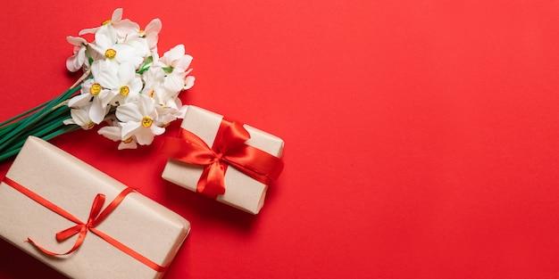 Wiosenna kompozycja. bukiet czerwonych kwiatów i pudełko na czerwonym tle.