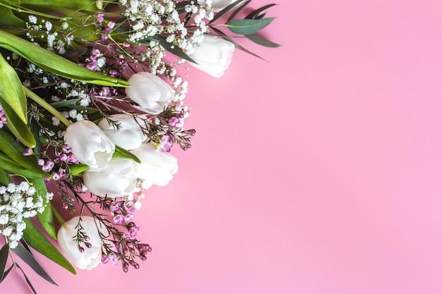 Wiosenna kompozycja kwiatowa na różowej ścianie