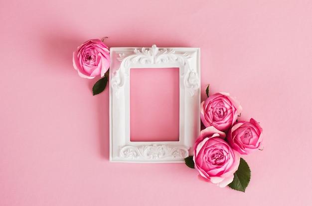 Wiosenna kompozycja kwiatowa świeżych róż i biała ramka tekstowa. ślub, urodziny, zaproszenie na dzień matki z miejscem na kopię