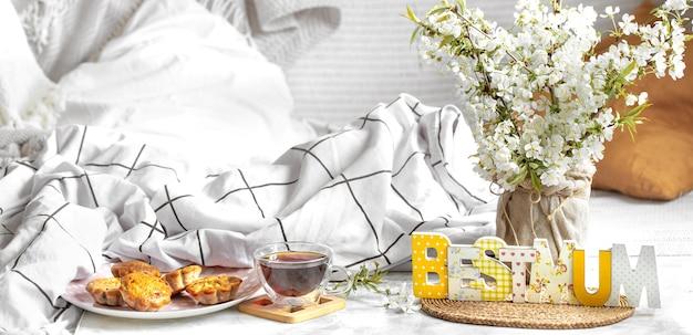Wiosenna kompozycja na dzień mamy z jasnym ozdobnym napisem najlepsza mama i herbatą z babeczkami na stoliku wygodnego łóżeczka.