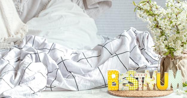 Wiosenna kompozycja na dzień matki z jasnym ozdobnym słowem najlepsza mama na łóżku.