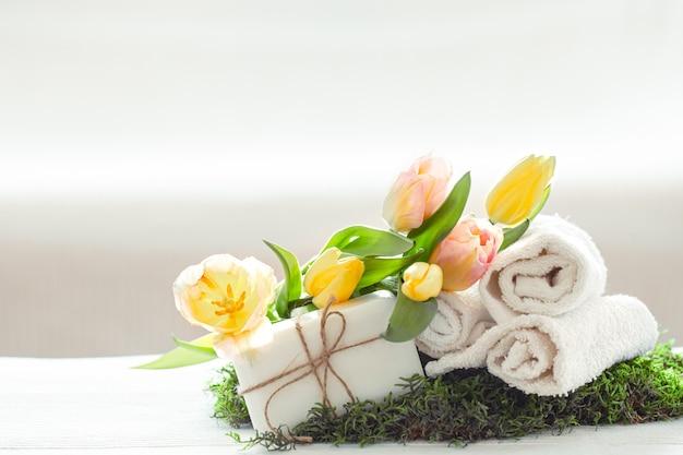 Wiosenna kompozycja spa z produktami do pielęgnacji ciała ze świeżymi tulipanami o świetle, pięknie i zdrowiu.