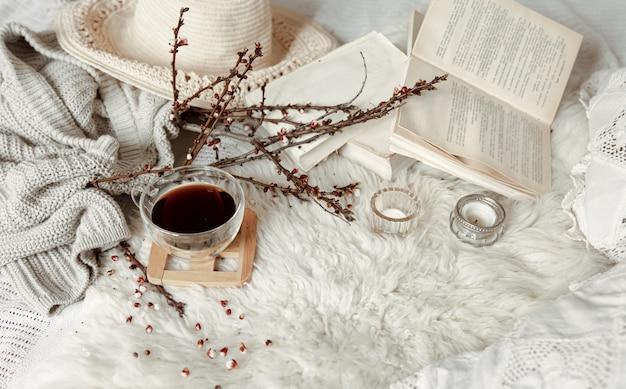 Wiosenna kompozycja z filiżanką herbaty, kwitnącymi gałązkami i detalami dekoracyjnymi.