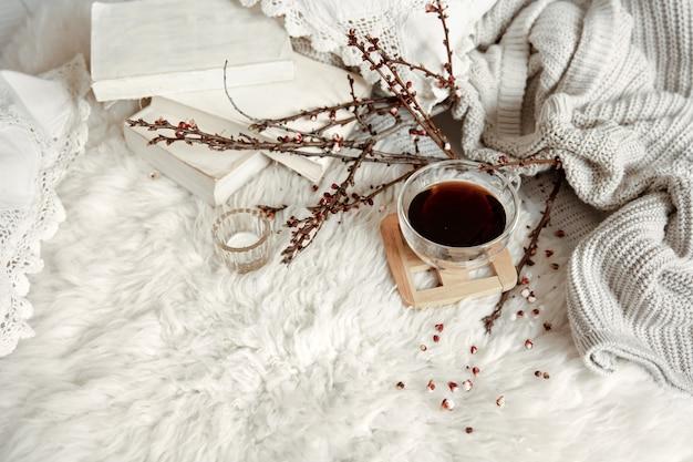 Wiosenna kompozycja z filiżanką herbaty, kwitnącymi gałązkami i dzianinowym elementem.