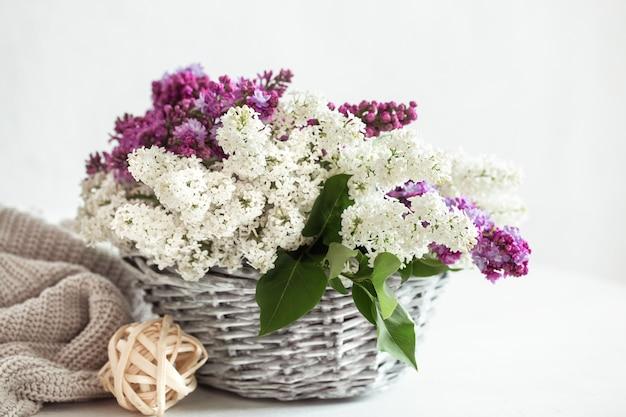 Wiosenna kompozycja z kolorowymi kwiatami bzu w wiklinowym koszu.