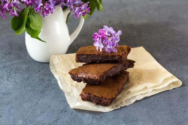 Wiosenna kompozycja z kwiatami bzu i brownie, mokre ciasto. deser przeznaczony na przerwę na herbatę lub kawę. przekąska w wiosenny dzień w ogrodzie.