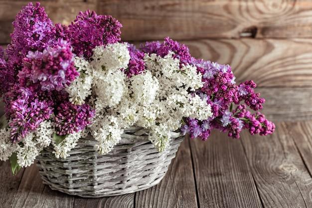Wiosenna kompozycja z kwiatami bzu w wiklinowym koszu. kosze upominkowe i koncepcja dostawy kwiatów.
