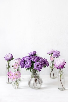 Wiosenna kompozycja z kwiatami chryzantemy w szklanych wazonach na niewyraźne białe tło, miejsce.