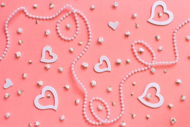 Wiosenna kompozycja z kwiatami, sercami i perłami na różowym tle