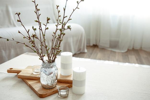 Wiosenna kompozycja z młodymi gałązkami w wazonie ze świecami we wnętrzu sali.