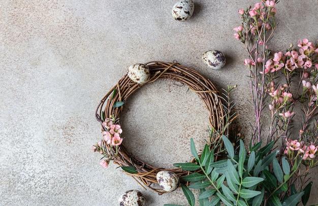 Wiosenna kompozycja z plecionym wiankiem z gałązek z kwiatami i jajkami przepiórczymi