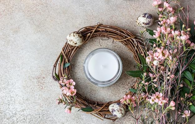 Wiosenna kompozycja z plecionym wiankiem z gałązek z kwiatami, jajkiem przepiórczym i świecą