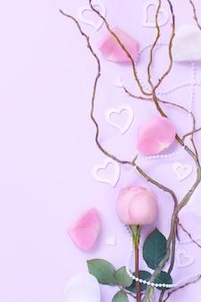 Wiosenna kompozycja z różą, płatkami i sercami na pastelowym tle