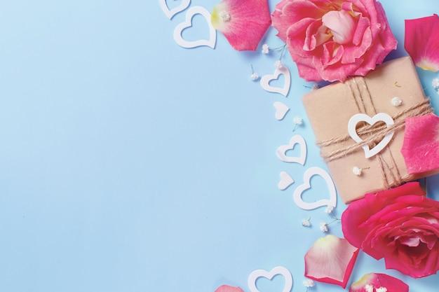 Wiosenna kompozycja z różami, płatkami, serduszkami i pudełkiem na pastelowym tle