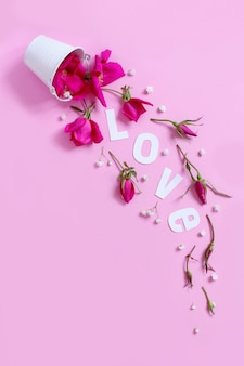 Wiosenna kompozycja z różowymi kwiatami i napisem love spadająca z białego wiadra