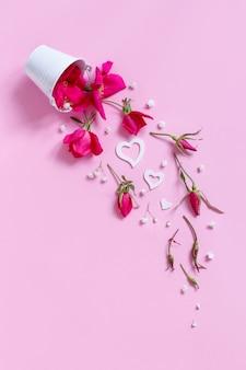 Wiosenna kompozycja z różowymi kwiatami i serduszkami spadającymi z białego wiadra