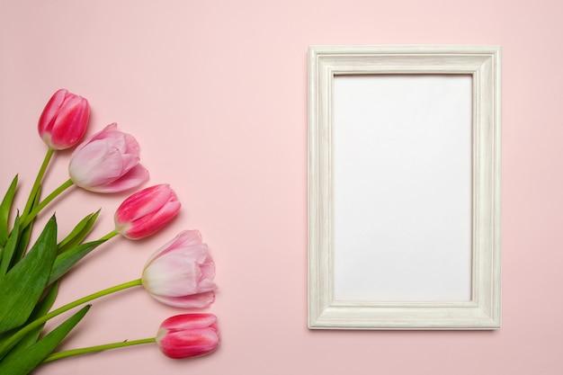 Wiosenna kompozycja z tulipanami na różowym tle, ramka na zdjęcia do wstawienia informacji.