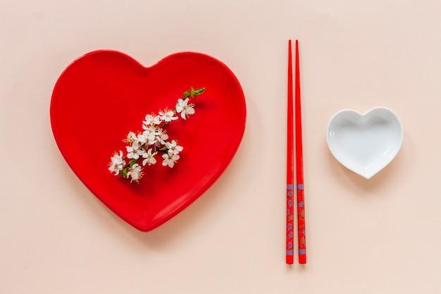 Wiosenna koncepcja japońskiego jedzenia z kwitnącymi gałęziami wiśni i serwująca z czerwonym sercem w kształcie naczynia i pałeczkami