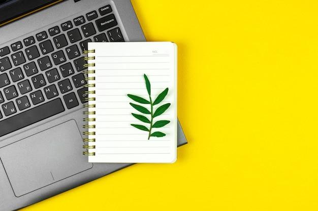 Wiosenna koncepcja obszaru roboczego, notatnik i pusty notatnik z zielonymi liśćmi, kreatywny płaski projekt dla witryny internetowej, miejsce kopiowania i żółte zdjęcie na pulpicie