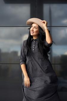 Wiosenna modna kolekcja odzieży damskiej. plenerowego portreta ładna młoda uśmiechnięta kobieta z długie włosy jest ubranym młodą szarą obszerną suknią i eleganckim kapeluszem w wietrznym dniu.