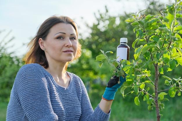 Wiosenna praca w ogrodzie, butelka nawozu chemicznego, fungicyd w ręce ogrodniczki