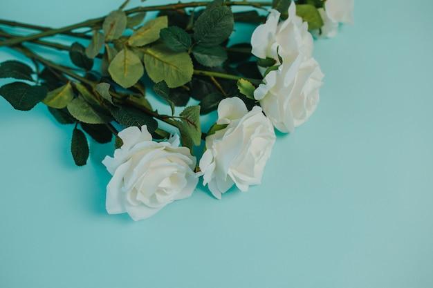 Wiosenna świeżość. białe róże z zielonymi liśćmi. bukiet pięknych białych róż z długą łodygą i miejsca kopiowania.