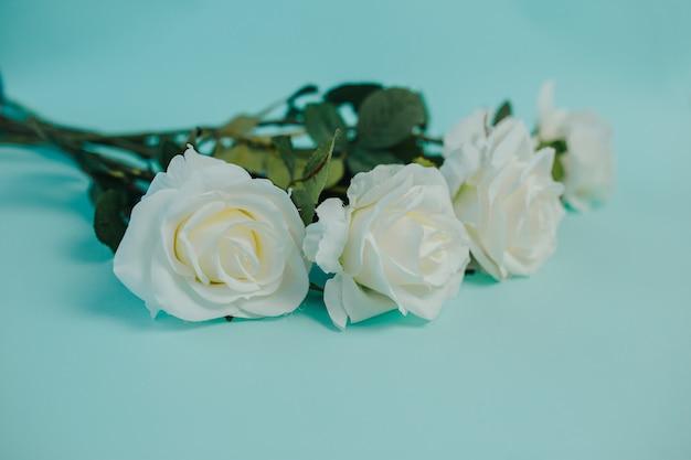 Wiosenna świeżość. białe róże z zielonymi liśćmi. bukiet pięknych białych róż z długą łodygą.