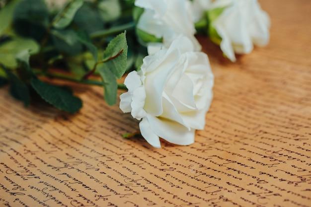 Wiosenna świeżość. białe róże z zielonymi liśćmi. piękne białe róże z długą łodygą na papierze pakowym.