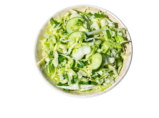 Wiosenna wegańska sałatka z kapustą, ogórkiem, zieloną cebulką i pietruszką na białym tle